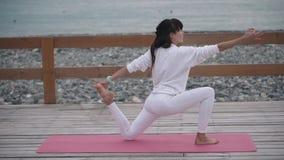 瑜伽教练员妇女在海岸做锻炼 影视素材