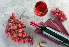 瓶、酒杯、葡萄和拔塞螺旋在灰色桌上 免版税库存照片
