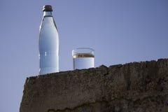 瓶和玻璃与冷的淡水反对天空 免版税图库摄影