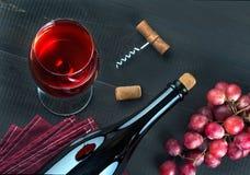 瓶酒、酒杯、葡萄和拔塞螺旋在黑暗的桌上 库存图片