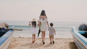 照相机与走在往美丽的晴朗的海洋海滩的小船之间的小孩一起跟随愉快的年轻女人 股票录像