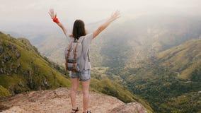 照相机平底锅在有举胳膊的背包的年轻愉快的旅游妇女后宽入空气在史诗山斯里兰卡 股票录像