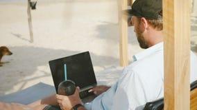 照相机在与果汁饮料的成功的愉快的fosuces商人掀动在海滩躺椅使用膝上型计算机在度假 股票录像