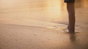 照相机在获得愉快的女孩掀动接触湿海滩沙子和泡沫似的波浪的乐趣进展在异乎寻常的日落海滩 股票视频