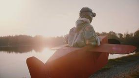 照相机跟随假装一点愉快的欧洲的男孩是乐趣服装的平面飞行员在日落森林湖慢动作 股票视频