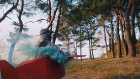 照相机跟随跑在森林佩带的乐趣纸板平面服装的愉快的飞行员男孩与小野鸭颜色烟慢动作 股票录像