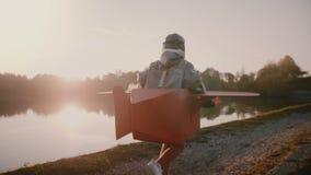 照相机跟随跑沿日落森林河的愉快的欧洲男孩扮演乐趣服装慢动作的飞机飞行员 股票视频