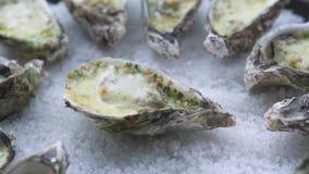 牡蛎烘烤用乳酪和草本在板材在海鲜餐馆 红色构成食物绿色瓶子油橄榄色的胡椒 地中海烹调用海鲜 影视素材