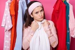 牢骚年轻女性拥抱白色女衬衫 美女佩带玫瑰色毛线衣和发带 有全部衣裳的翻倒女孩 免版税库存照片
