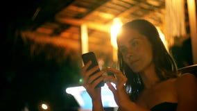特写镜头在网上被射击夜休息室海滩咖啡馆的愉快的轻松的年轻女实业家使用智能手机电子商务应用程序 股票录像