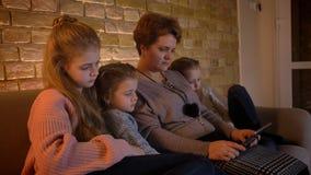 特写镜头在观看入有巨大兴趣的片剂的白种人母亲和女儿档案的家庭画象在舒适 股票视频