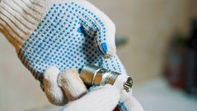 特写镜头手套的手一个人在铁水龙头螺丝附近密封磁带套 影视素材