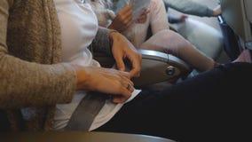 特写镜头紧固安全带的被射击女性手在去飞机的飞行期间假期与家庭,安全概念 股票录像