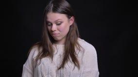 特写镜头画象年轻可爱的白种人深色的女性困窘和被混淆的微笑,当看时 股票视频