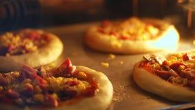 特写镜头,烘烤从发酵面团的微型比萨的过程在一个大工业烤箱 在工业的烘烤的面包 股票视频