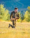 狩猎射击战利品 与寻找动物的步枪的猎人 人充电的狩猎步枪 寻找作为男性爱好和 免版税图库摄影