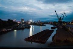 相当港口在城市起重机和船坞-夜视图 库存照片