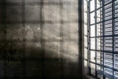 监狱牢房的非常清醒的内部:与进来一点的光和光秃的混凝土墙的禁止的窗口 库存照片