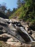 瀑布从高岩石流动到小河和豪华的森林 免版税库存图片