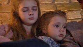 白种人两女儿特写镜头画象观看入有巨大兴趣的片剂的在舒适家庭环境上 股票录像