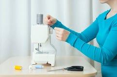 白种人女孩跑在缝纫机的螺纹 特写镜头 库存图片
