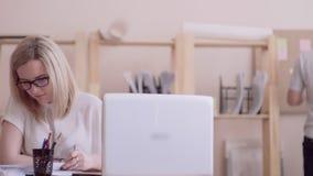 白种人出现的女孩与玻璃努力工作的在桌文字的办公室在背景中的看膝上型计算机 股票录像
