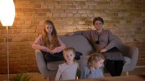 白种人母亲家庭画象有三个女儿的坐沙发和电影在舒适家庭环境 影视素材