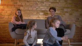 白种人母亲家庭画象有拥抱在舒适家庭环境的三个女儿的和电影 股票录像