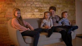 白种人母亲家庭画象有笑着一起坐三个的女儿和电影的在舒适家 股票视频