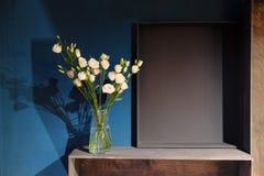 白玫瑰花束在一个玻璃花瓶的站立对深蓝墙壁 搁置木 免版税库存图片