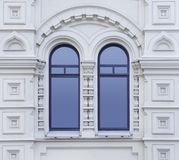 白色古老大厦门面与装饰装饰品和两部分被成拱形的窗口的作为纹理 库存图片