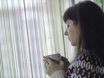 白色杯子用茶在支持窗口的年轻女人的手上 免版税库存照片