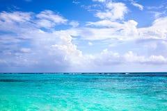 白色沙滩,天空蔚蓝的绿松石海有白色云彩背景 免版税库存照片