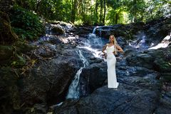 白色礼服的年轻女人摆在瀑布 图库摄影