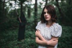 白色礼服的年轻女性受害者在森林里 库存图片