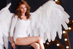 白色紧身衣裤的年轻女人与天使翼 免版税库存图片