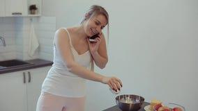 白色衬衫的美丽的白种人女孩和桃红色烹调在轻的厨房里,谈话在手机和微笑 股票录像