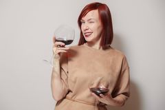 白色背景微笑、闪光和举行的年轻快乐的红发女孩斟酒服务员有两杯的红酒 概念工作与 免版税库存图片