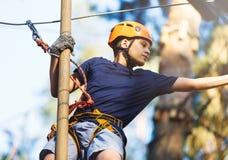 白色T恤杉的运动,年轻,逗人喜爱的男孩在公园在冒险绳索公园盔甲的和安全设备花费他的时间 库存照片