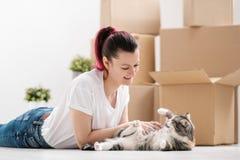 白色T恤的年轻美丽的深色的女孩在轻的屋子的地板上说谎并且使用与猫 aromaticity 免版税图库摄影