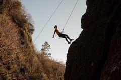 用绳索装备的亭亭玉立的适合的女孩abseiling在倾斜的岩石 免版税库存照片