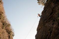用绳索装备的坚强的妇女abseiling在倾斜的岩石 图库摄影
