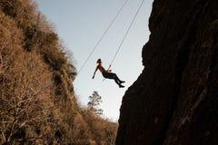 用绳索装备的女孩abseiling在倾斜的岩石和看下来 免版税库存照片