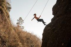 用绳索装备的女孩abseiling在倾斜的岩石 免版税库存照片