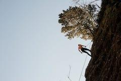 用绳索装备的妇女abseiling在倾斜的岩石 免版税库存照片