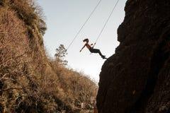 用绳索装备的运动的女孩abseiling在倾斜的岩石 免版税库存照片