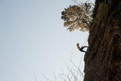 用绳索装备的运动的妇女abseiling在倾斜的岩石 库存照片