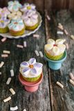 用黄油奶油和蛋白软糖花装饰的杯形蛋糕 免版税库存照片
