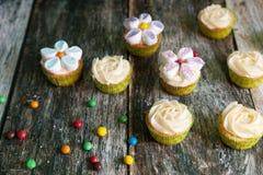 用黄油奶油和蛋白软糖花装饰的杯形蛋糕 免版税图库摄影