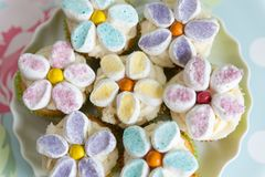 用黄油奶油和蛋白软糖花装饰的杯形蛋糕 库存照片